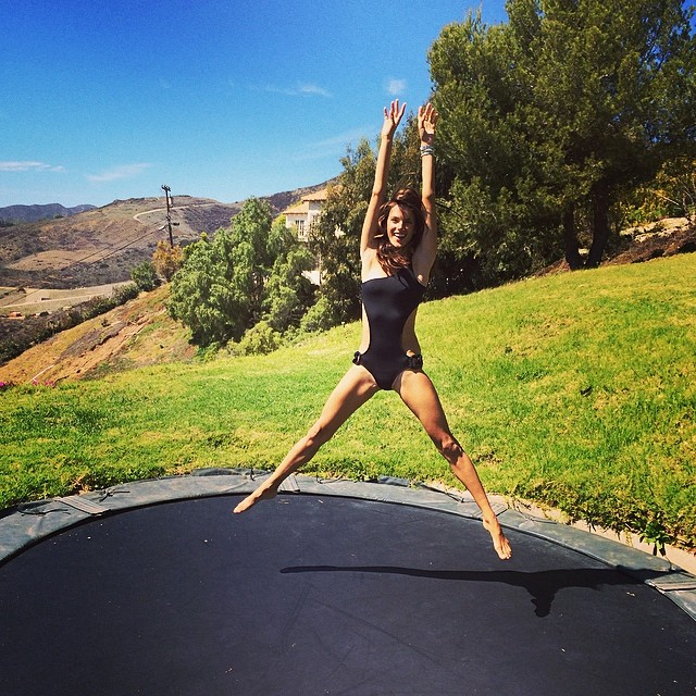 Alessandra Ambrosio jumps on a trampoline in her swimsuit