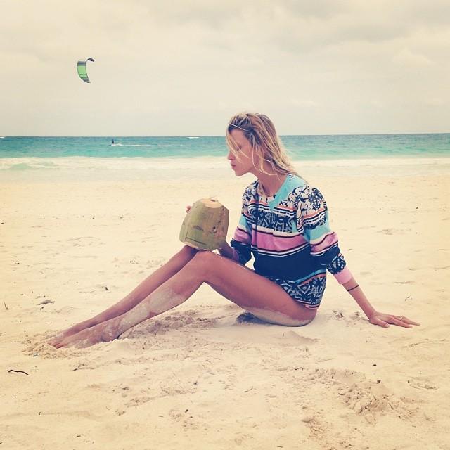 Anja Rubik enjoys a coconut on the beach