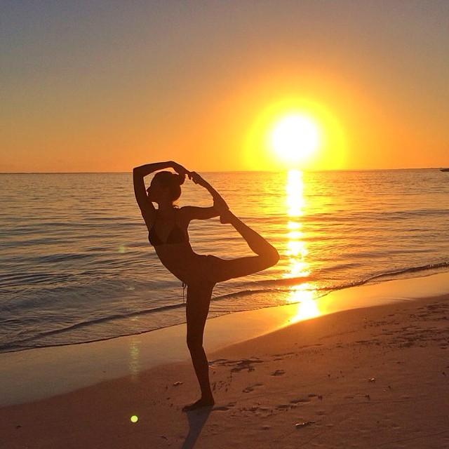 Gisele Bundchen does a yoga pose on the beach
