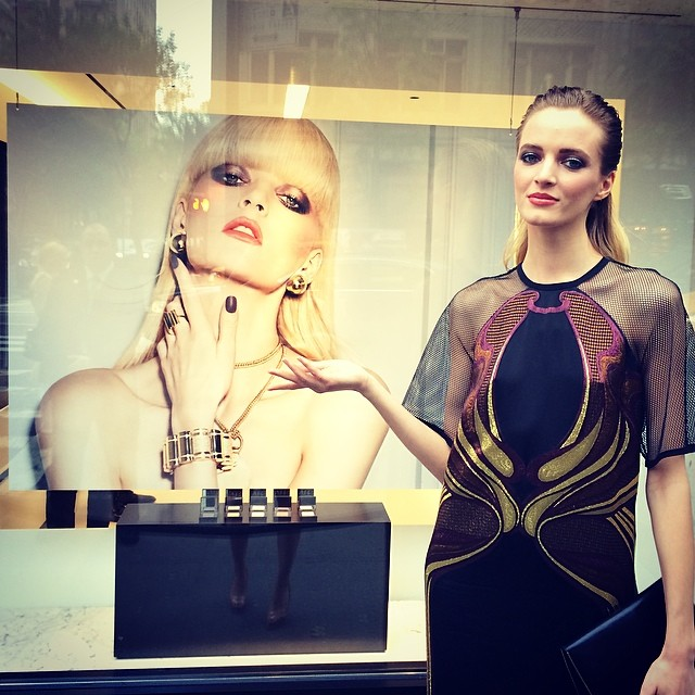 Daria Strokous poses next to her NARS' ad