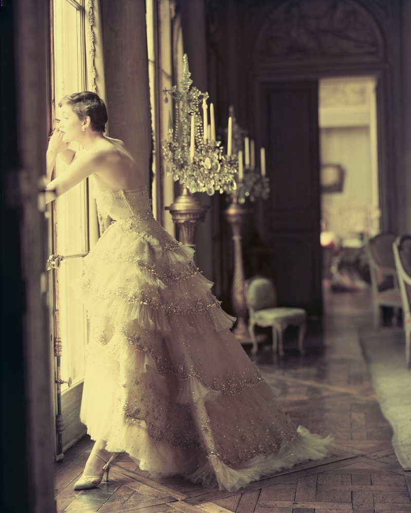 ca. May 1950 --- A fashion model peers out the window of an elegant home wearing a white Christian Dior evening gown decorated with tiers of ruffles. --- Image by © Norman Parkinson/Corbis