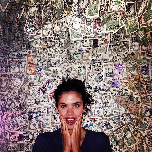 Sara Sampaio poses next to money wall