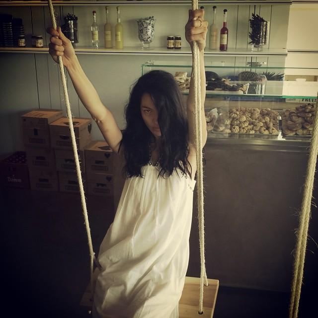 Mariacarla Boscono poses on a swing