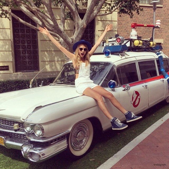 """Cara Delevingne poses with a """"Ghost Busters"""" car"""