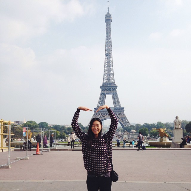 Liu Wen takes a photo near the Eiffel Tower in Paris