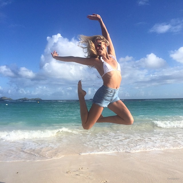 Rachel Hilbert jumps in a bikini top and denim shorts while in St. Barths for VS Pink