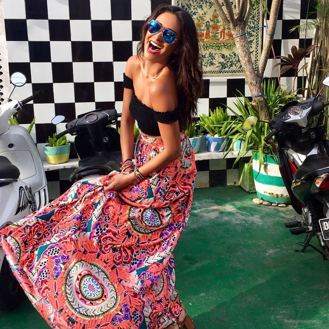 The actress wears a black top with a colorful skirt