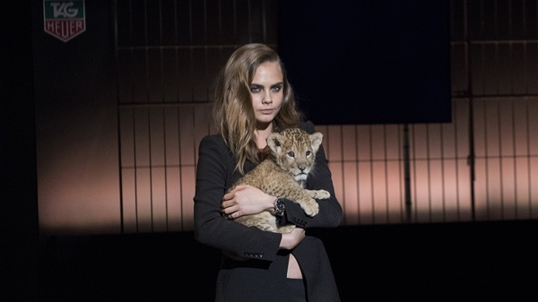 Cara Delevingne poses with baby lion cub at TAG Heuer event
