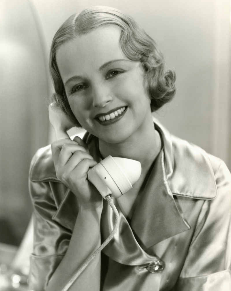 Posing with a smile, a woman wears 1930s sculpted waves. Photo: Deposit Photos