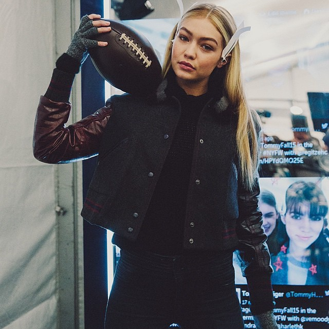 Gigi Hadid poses with a football at the Tommy Hilfiger show