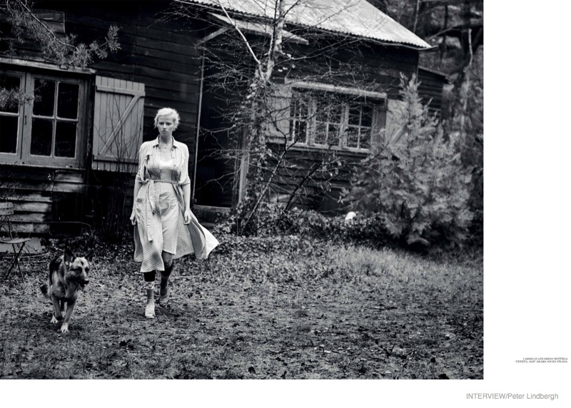 A Bottega Veneta cardigan and dress clothes Lara as she poses in front of a cabin