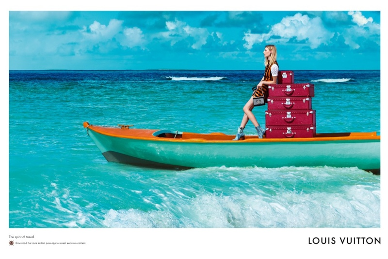 Julia Nobis poses on a boat with suitcases while wearing a colorful dress from Louis Vuitton.
