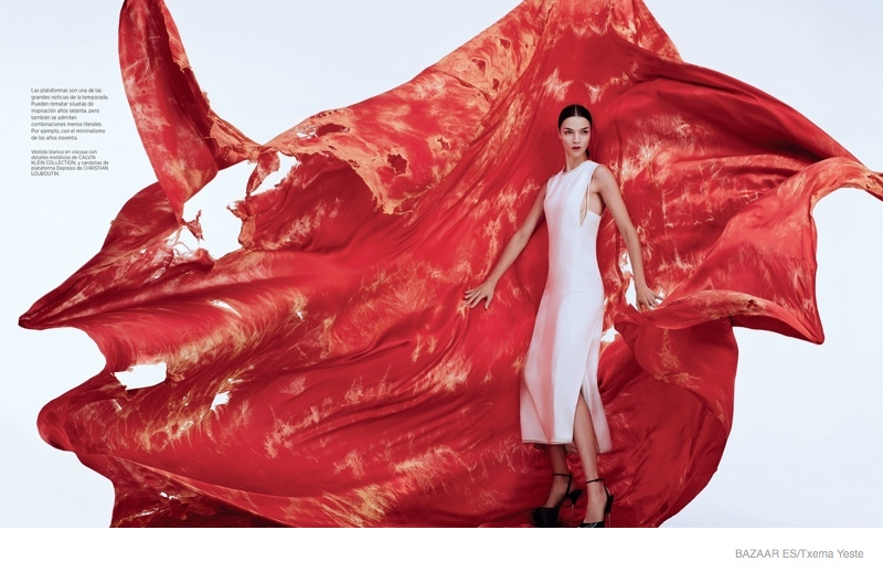 With tattered red fabric behind her, Mariacarla stuns in a white Calvin Klein Collection dress