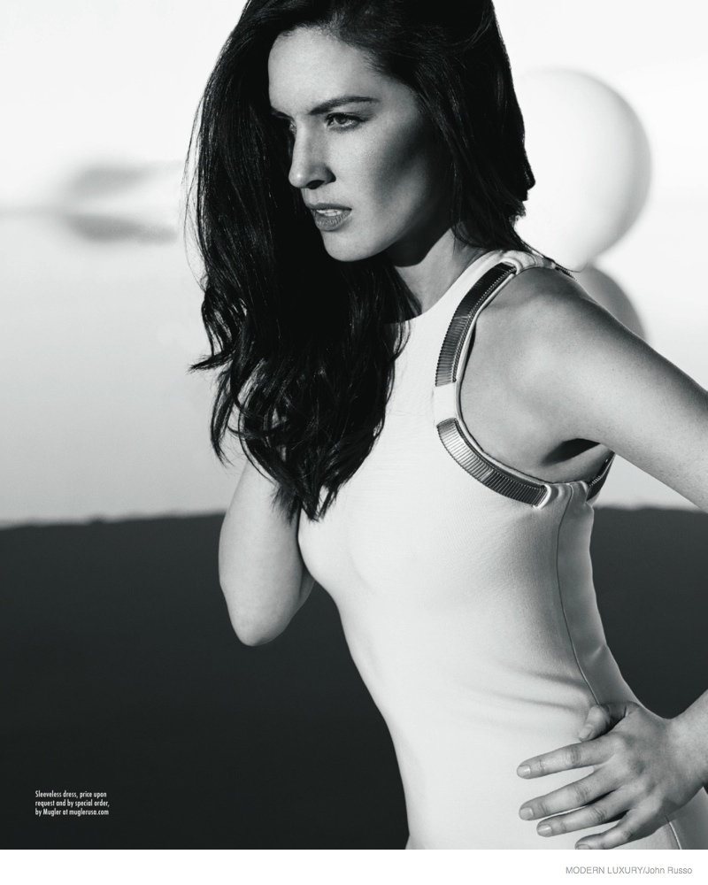 A sleeveless white dress with metal details from Mugler covers Olivia in this black and white image.