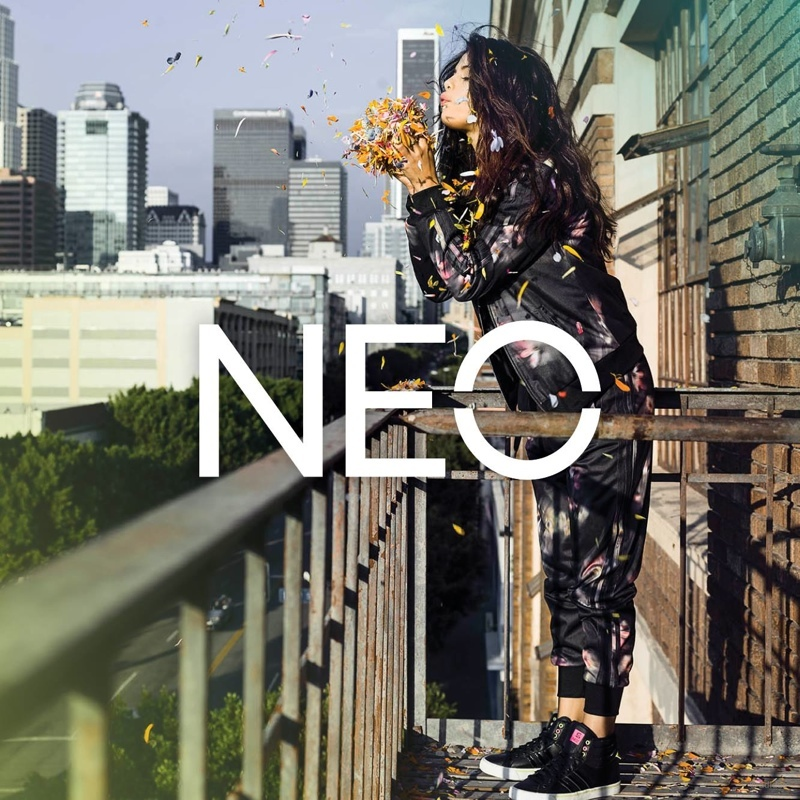 Selena Gomez blows on flower petals in a promotional shot for adidas NEO spring 2015.