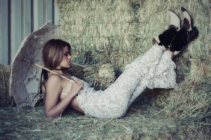 Hailey models a white lace dress in hay.