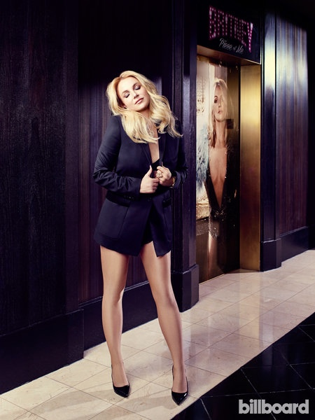 Posing next to a promotional poster of herself, Britney Spears flaunts her legs in Billboard feature.