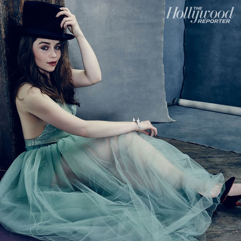 Emilia looks radiant in a a green dress and black hat.