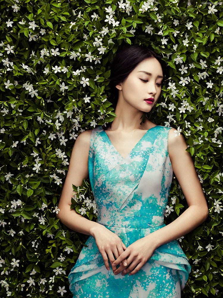 Posing against a wall of flowers, the model looks ready for spring