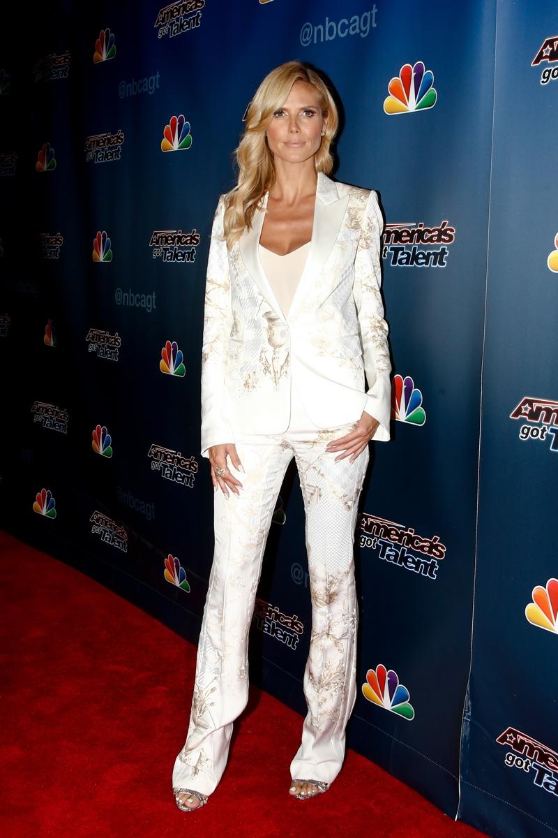 Hedi Klum sports a white Roberto Cavalli pant suit with gold embellishments. Photo: Shutterstock.com
