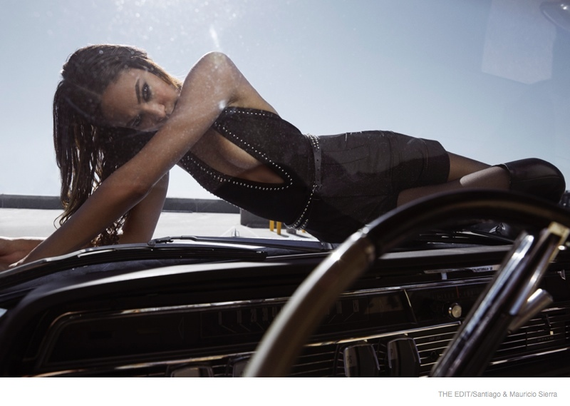 Wearing a bodysuit and shorts from Givenchy, Joan stuns while posing on top of a car.