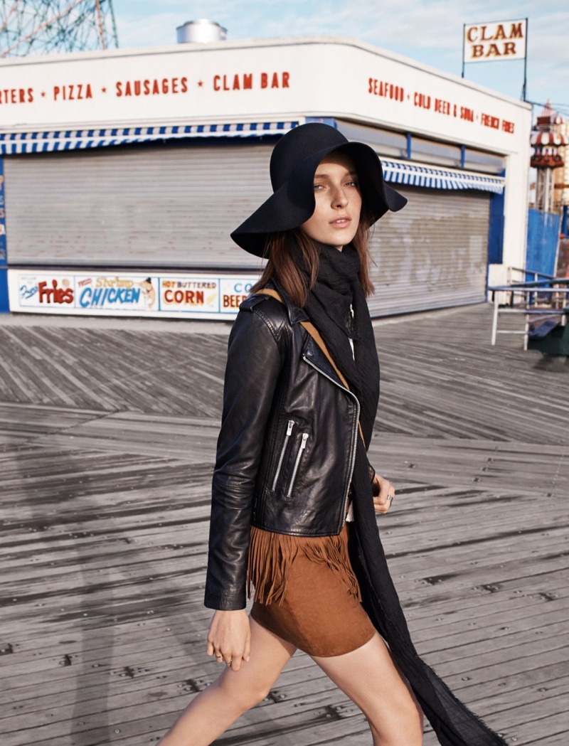 Posing in Coney Island, Julia wears a mini skirt, leather jacket and floppy hat.