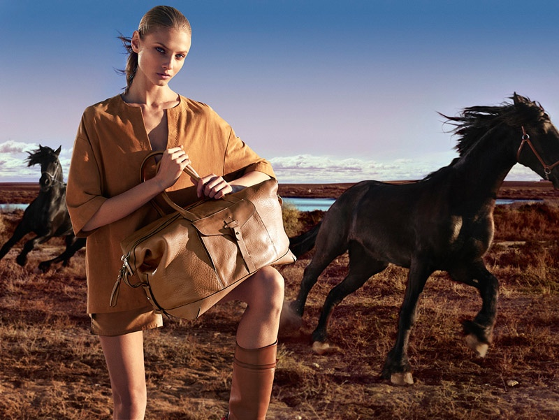 Anna Sezneva models a large tote, riding boots and an oversized shirt from Massimo Dutti.