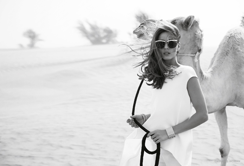 Clad in white and wearing sunglasses, Olivia looks ready for a trek in the sand.