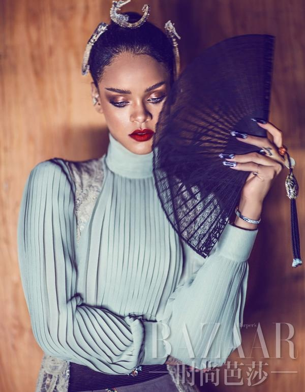 A blue blouse and fan are modeled by Rihanna for Bazaar China.