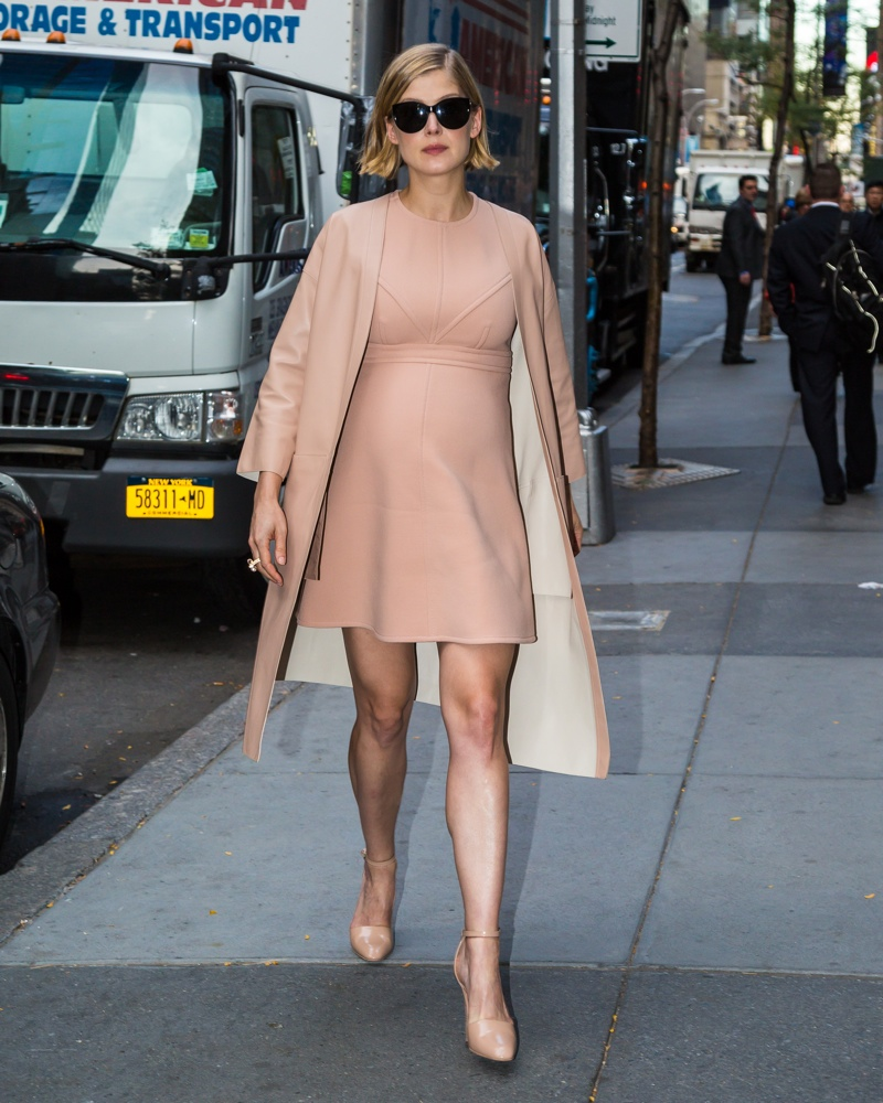 Showing off maternity style, Rosamund Pike hit the streets in a short dress and matching coat. Photo: Shutterstock.com