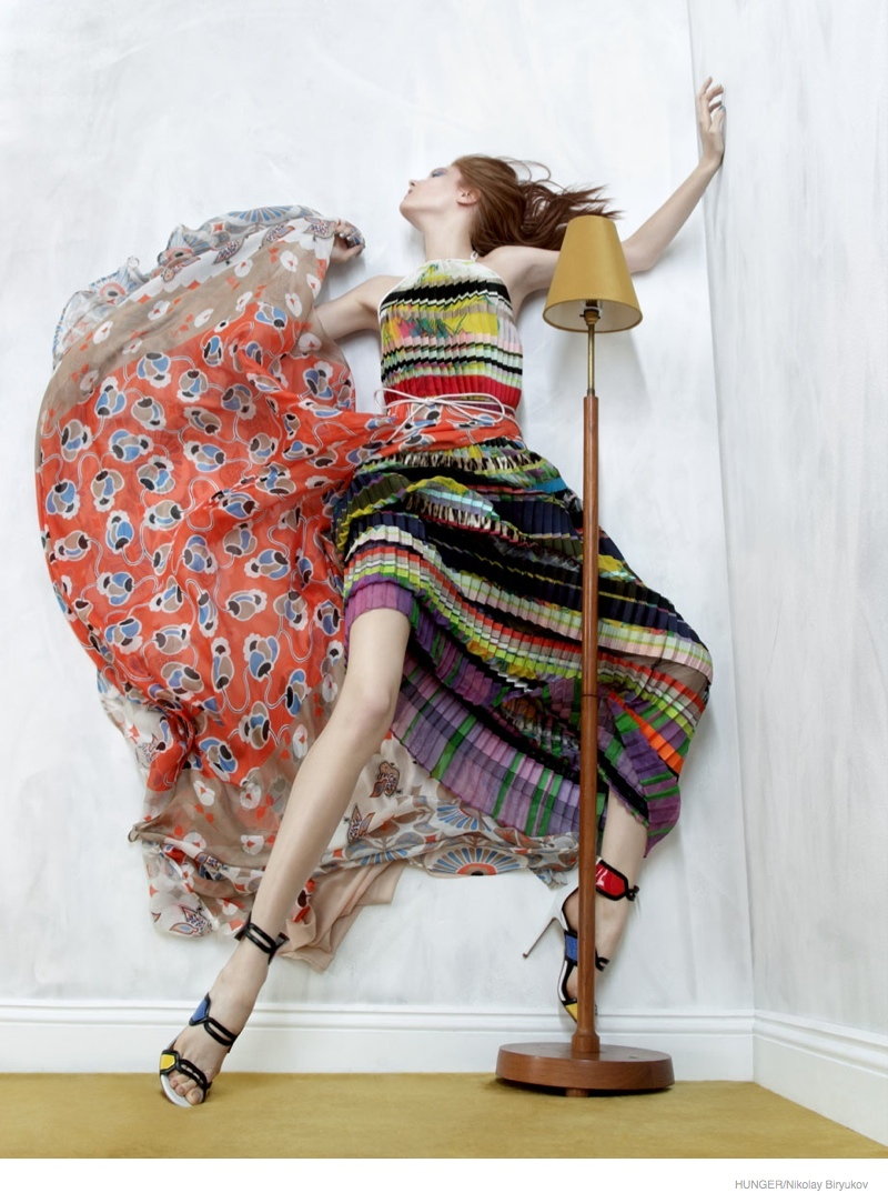 Wearing a rainbow colored dress, Anastasia clings to the walls.
