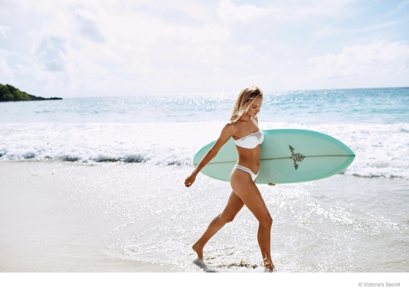 Candice Swanepoel hits the beach with a surf board for VS Swim catalogue.