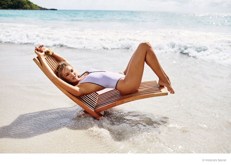 Wearing a one-piece look, Candice stuns on white sand beaches.
