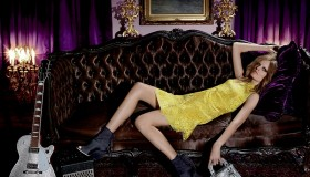 Hanne lounges in a yellow Dior dress with a guitar by her side