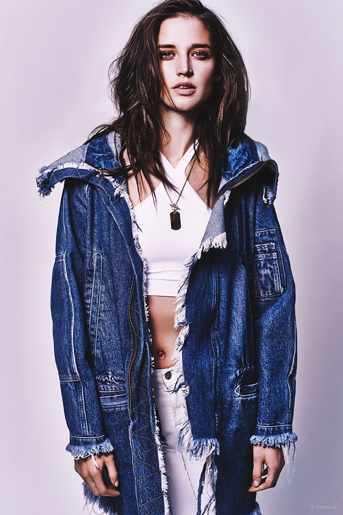 The model wears a R13 denim jacket, Helmut Lang bra top and J Brand high rise jean leggins