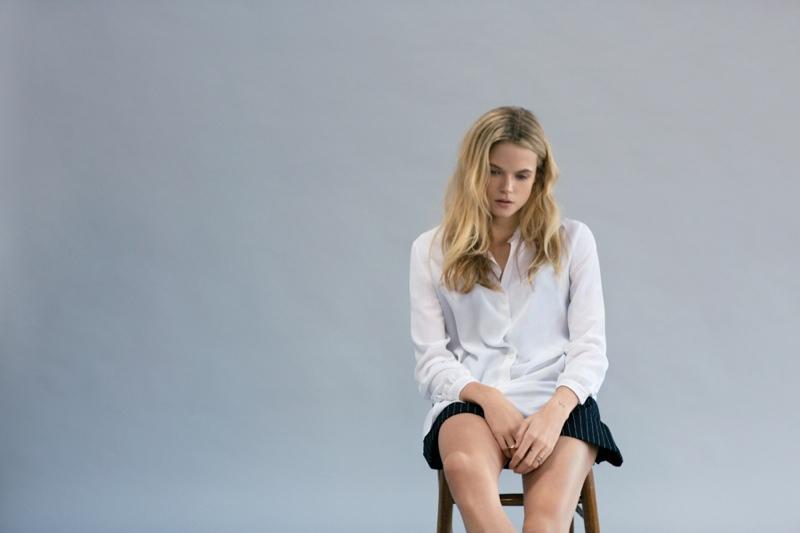 Gabriella wears a white shirt and black skirt