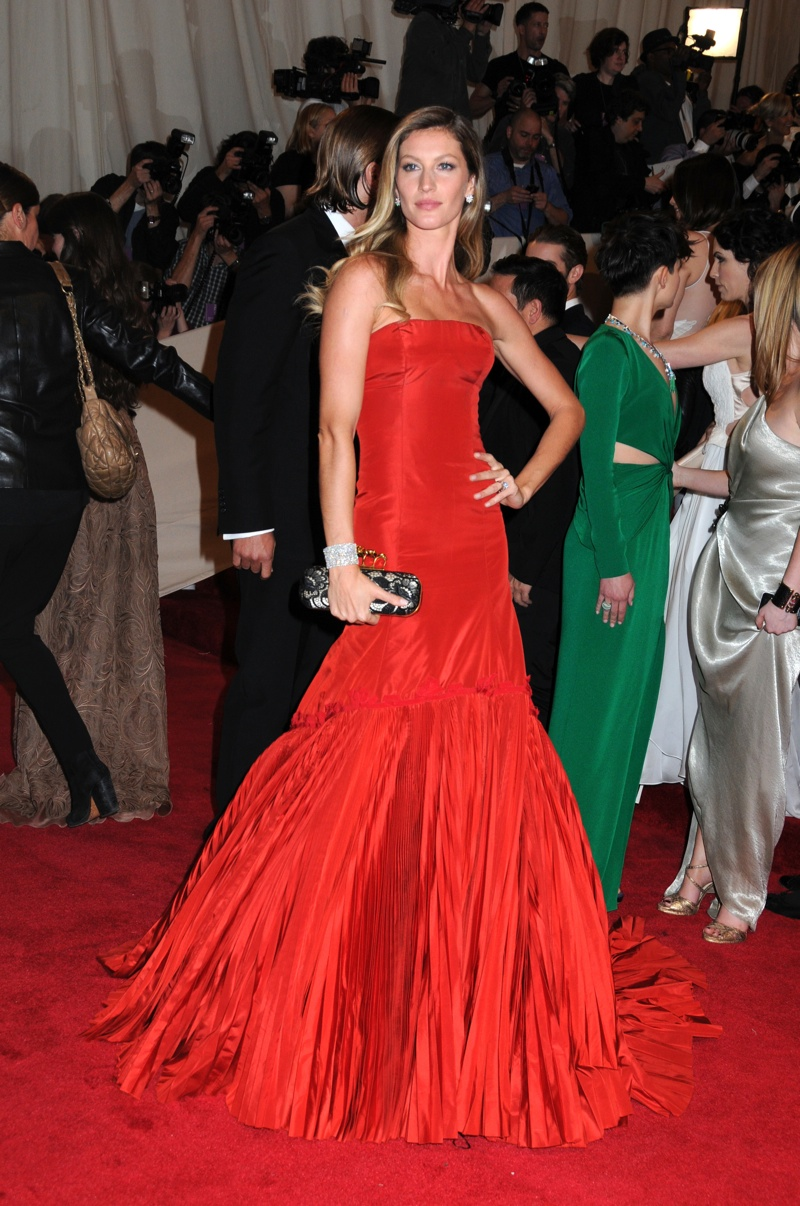 Supermodel Gisele Bundchen looked stunning in a red column dress with a flared and pleated skirt at the 2011 Met Gala which paid tribute to Alexander McQueen. Photo: Janet Mayer / PR Photos