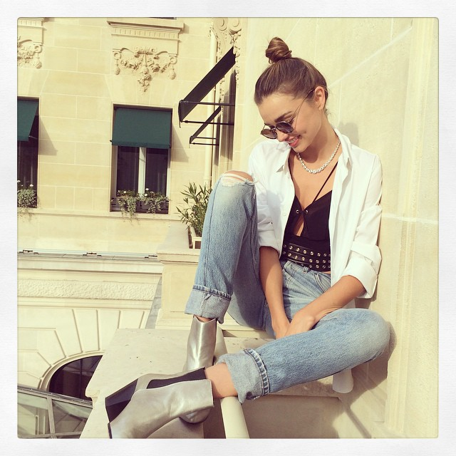 The Australian model keeps it casual in ripped denim with a white shirt and black tank. Photo via Instagram.