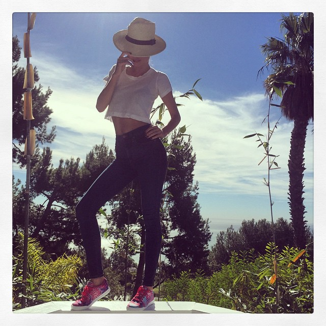 Covering her face, Miranda rocks a high-waist skinny denim pant with Reebok shoes and a hat. Photo via Instagram.