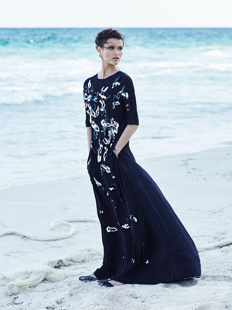 Chloe wears a dark dress with sequin embellishments