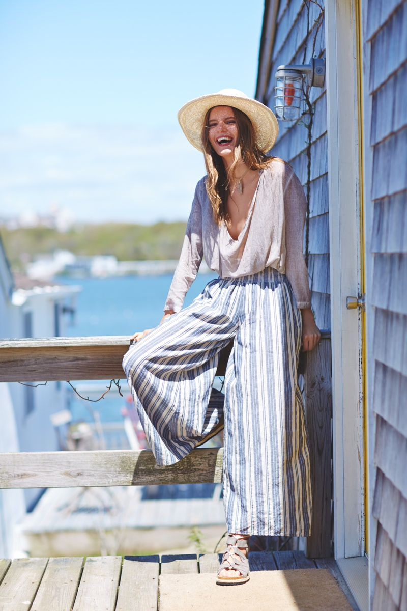 Tilda models wide-legged pants, a straw hat and loose blouse