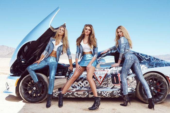 Clad in denim, the girls pose next to racing cars