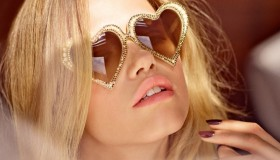 The blonde model wears a pair of heart shaped sunglasses