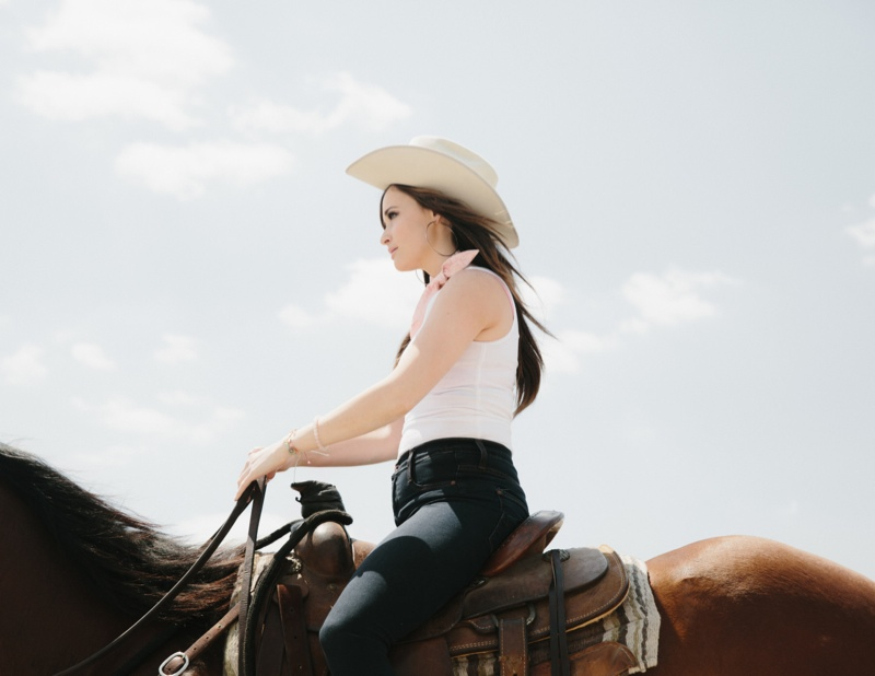 Kacey rides a horse for the photo shoot