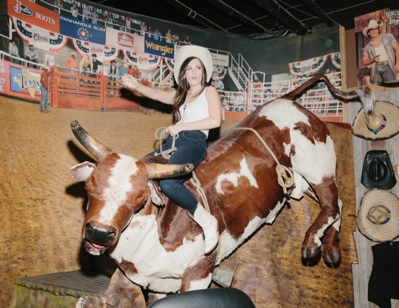 Kacey rides a mechanical bull while sporting a cowboy hat, denim pants and western style boots