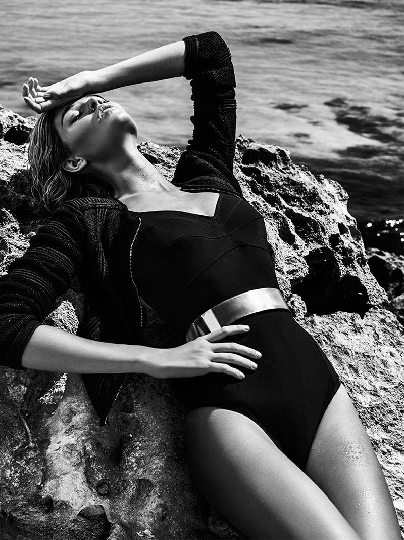 Luisa poses beachside in a one-piece swimsuit with a cropped jacket