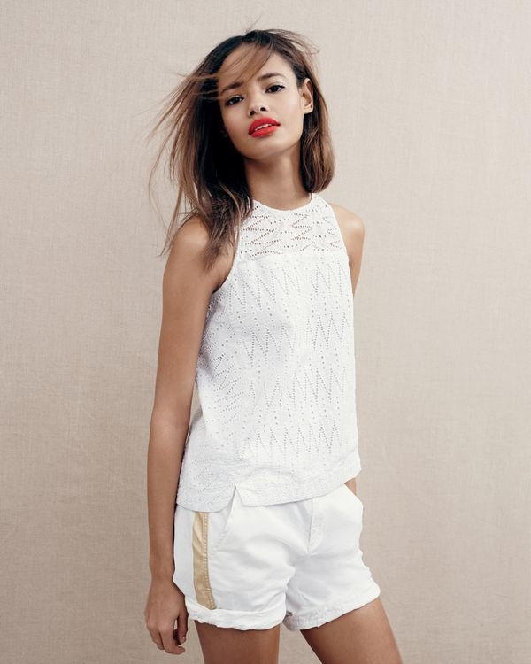 Malaika wears a white eyelet top with a gold striped short