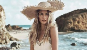 Natasha wears an oversized straw hat with a white maxi dress