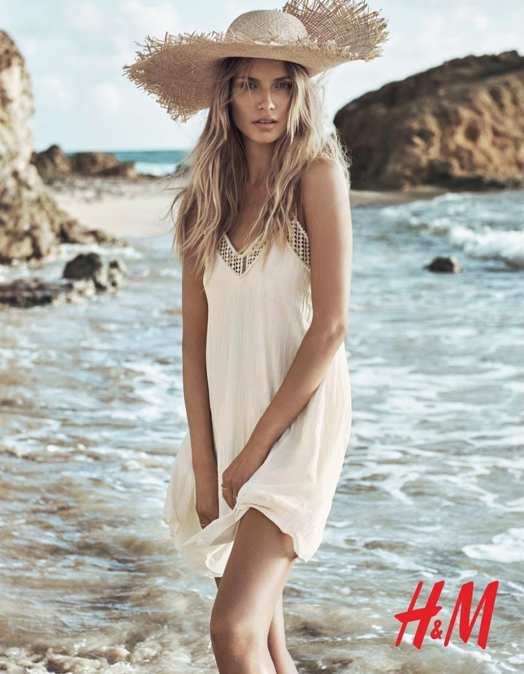 Natasha wears an oversized straw hat with a white maxi dress