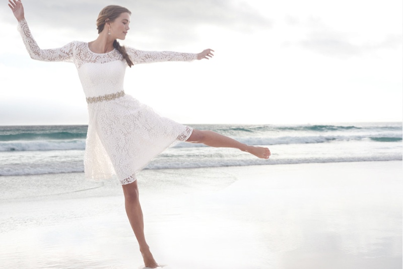 A model poses on the beach in a white lace dress